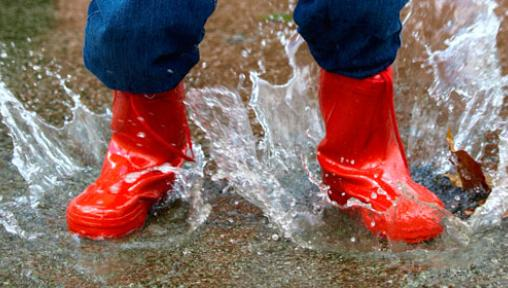 child in rain boots splashing in puddle